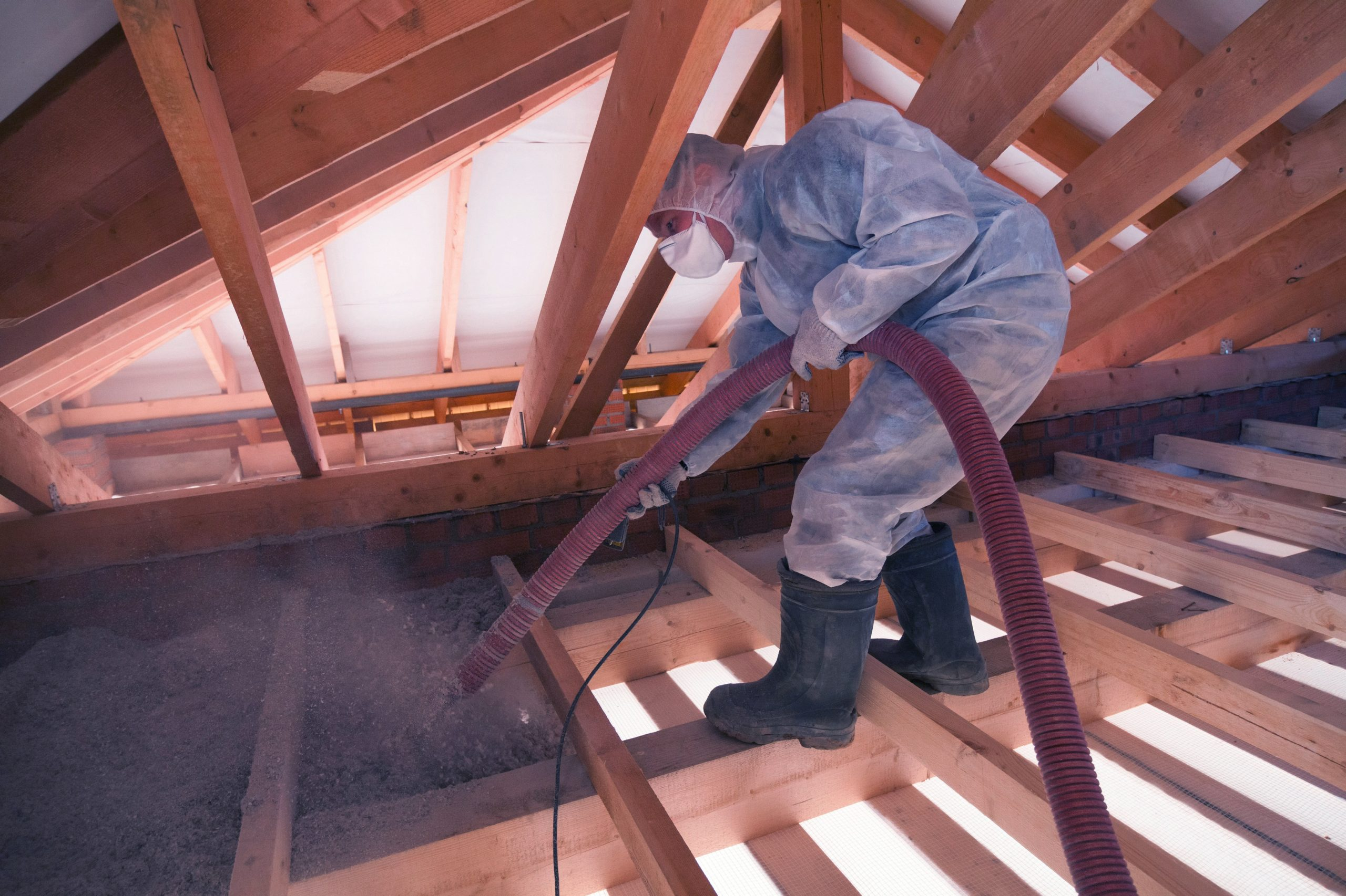 contractor in an attic performing blow-in fiberglass insulation services